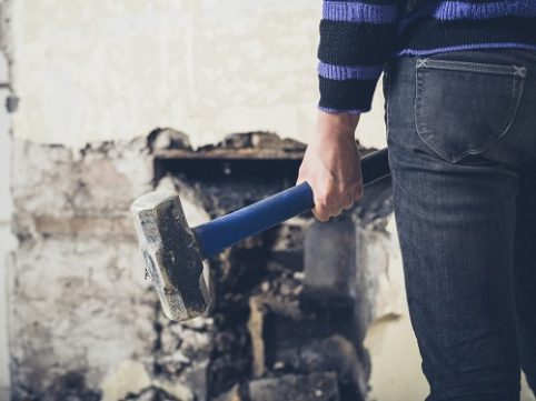 A young woman is opening up an old fireplace in a Victorian house with a sledge hammer